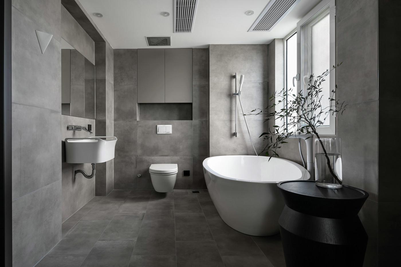 卫浴空间很宽敞,通体灰色瓷感经典简约,局部使用白色洁具搭配,增强整体美观度,浴缸与淋雨相互结合,简约