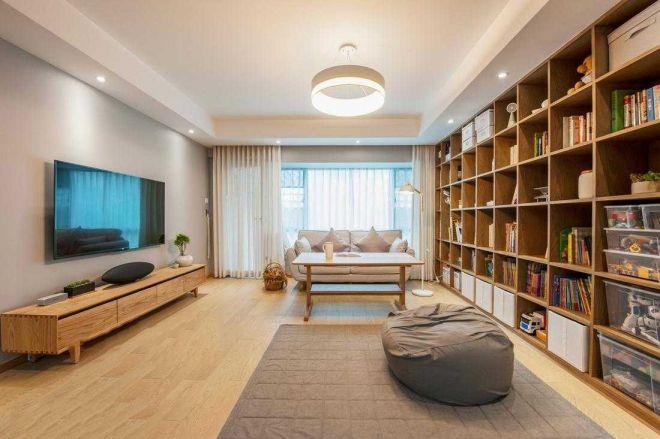 与常见的沙发面朝电视不同,沙发摆放在阳台处,光线充足,客厅设计大面积书柜,也是受很多年轻人喜欢的风格