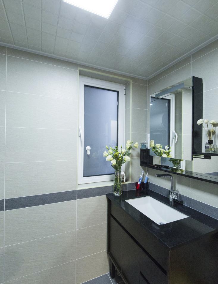 洗手间用大块素色墙砖营造低调,简单的镜子很职场。