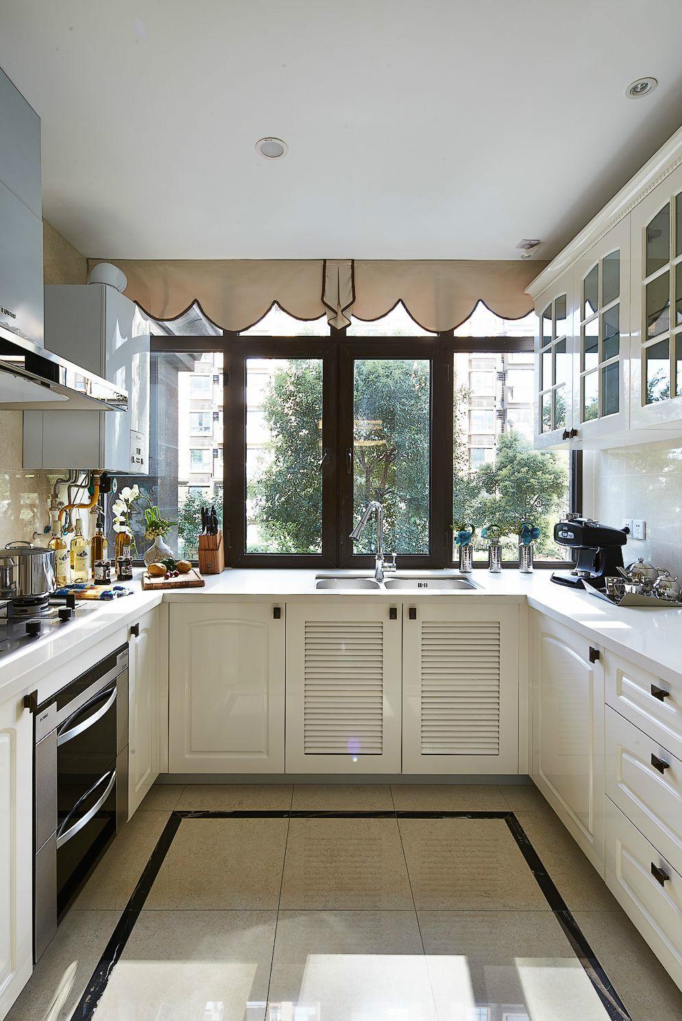 厨房采用了U型设计,作业面广非常实用;宽大的窗台照在白净的橱柜上,明亮宽敞。