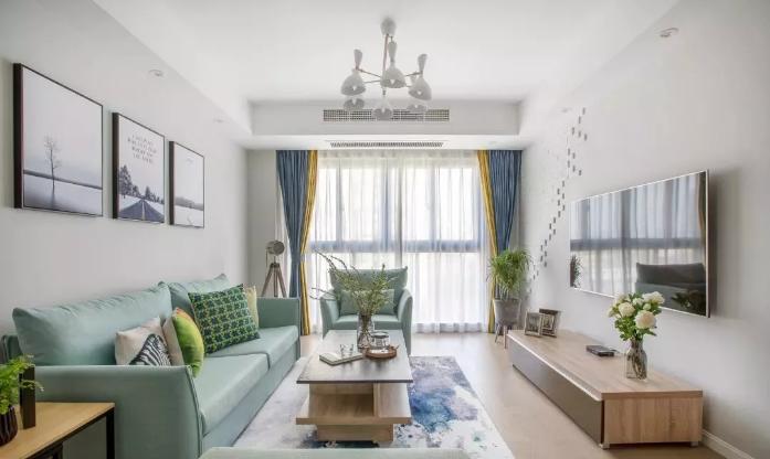 客厅空间自然清新,大白墙搭配蓝绿色沙发,以及自然木纹电视柜、茶几、边几等家具,整体格外的自然清新。