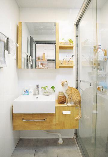 卫生间设计为干湿分区。洗漱台延续整体的风格,温润木色搭配简约白色,狭窄的空间有了一点也不局促的视觉。