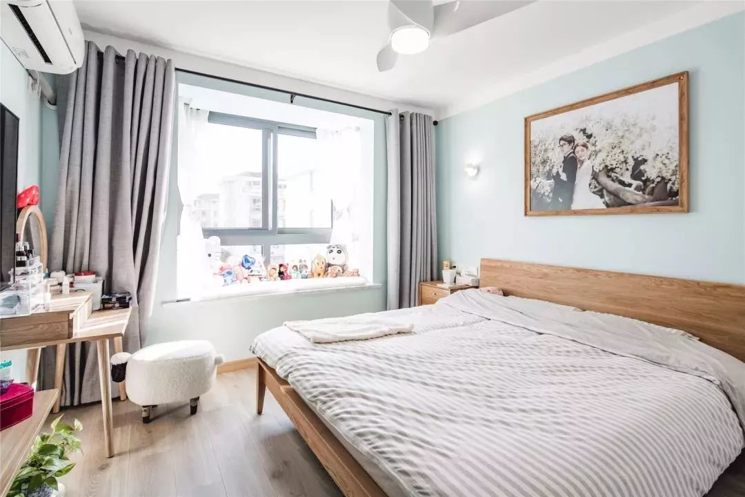 主卧淡蓝色的墙壁,小清新的感觉,床头背景墙上没有复杂的设计,一幅浪漫唯美的婚纱照,定格在了美丽的瞬间