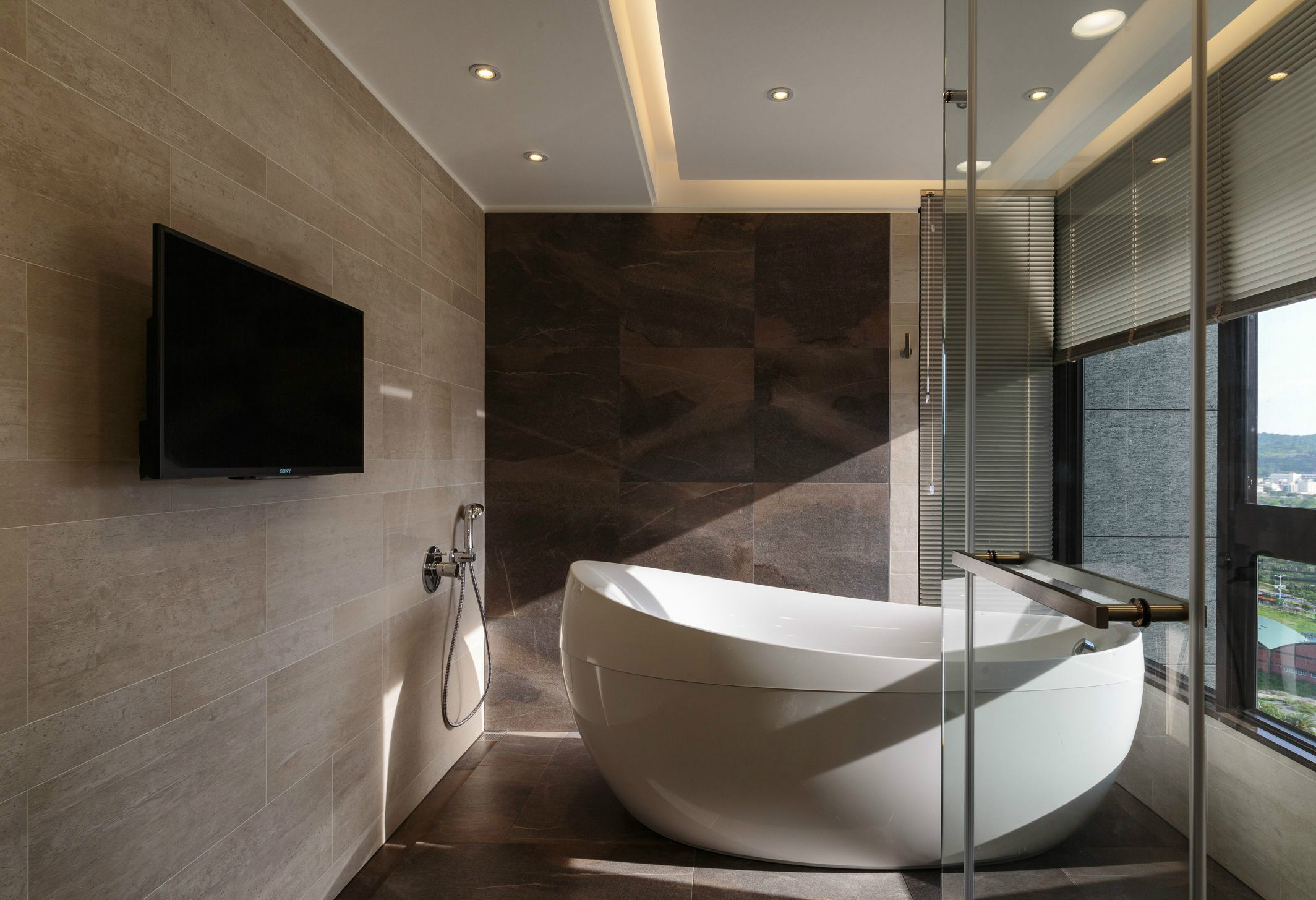 卫生间是一个简单大气的白色浴缸,在阳台旁边很是美观