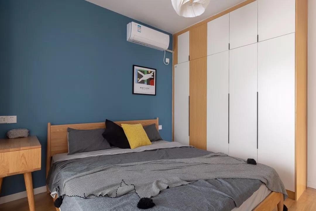 嵌入式衣柜木色与白色结合,提升室内温馨感,灰色床品与蓝色背景墙相互融合,提升卧室品质。