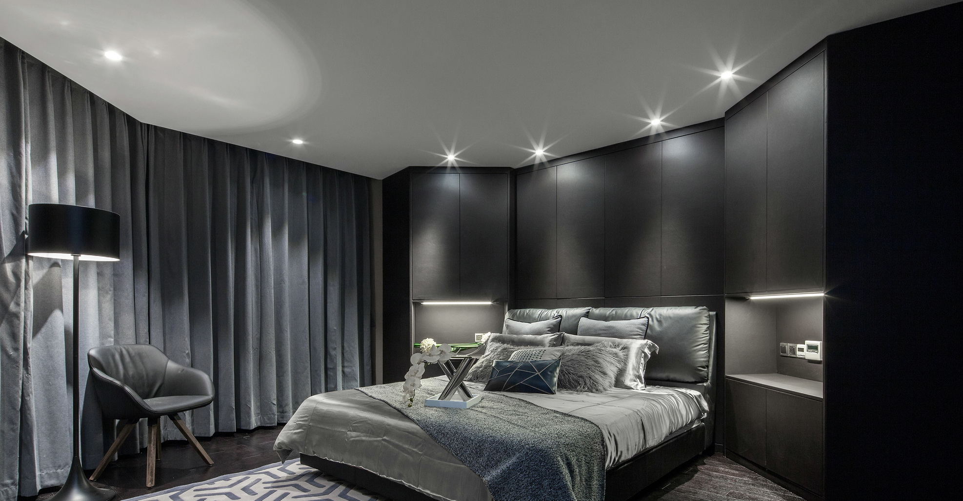 卧室中放置着简约的大床,搭配上以黑灰为布艺床品,