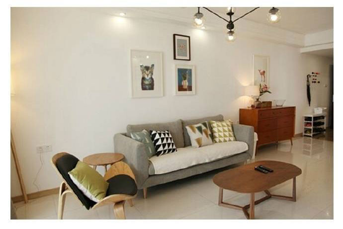 客厅铺着浅色的地砖,沙发是一款灰色的布艺沙发。