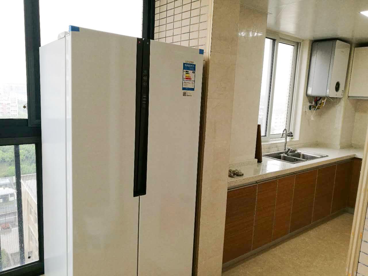 双开门冰箱放置在厨房门口,方便存取食物。