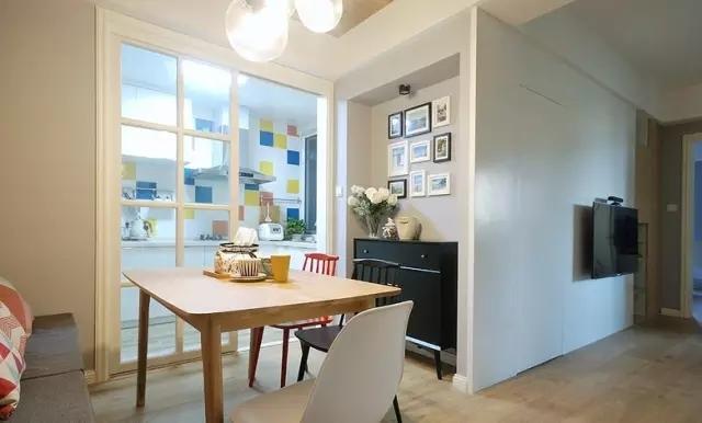 从餐厅望向厨房,厨房用透明的格子门打造通透感,这样的推拉门比平开门更适合拥挤的小空间。
