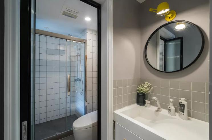卫生间做了干湿分离,地面和墙面还是主色调低调的浅灰色,圆形镜子上有一个黄色的小臂灯,用来补充照明。