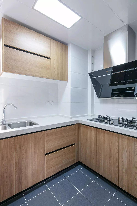 厨房地面铺贴深灰色瓷砖,墙面铺贴白色仿石纹瓷砖,木色橱柜隐形拉手的设计,整体更为干净利落。