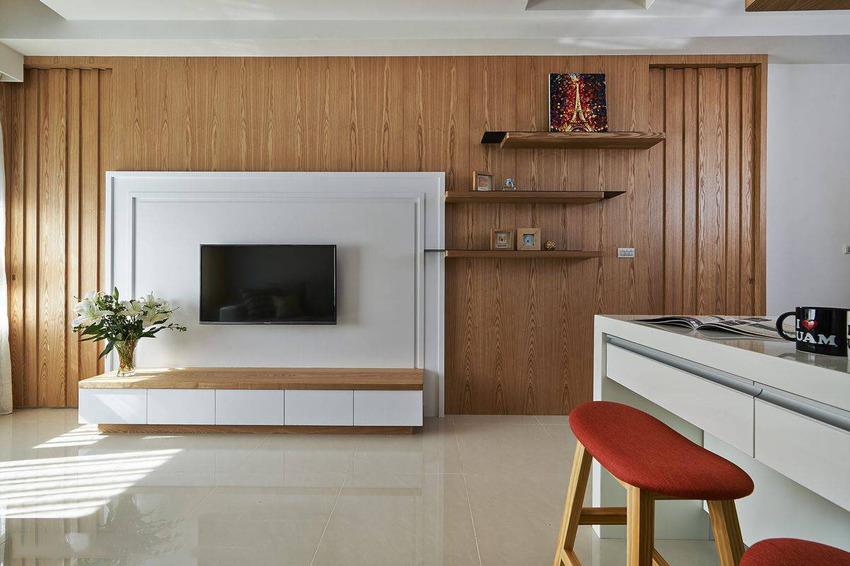 大跨距的钢刷木皮立面,以白色线板框作为电视主墙,材质的堆衬创造立体的视觉层次。