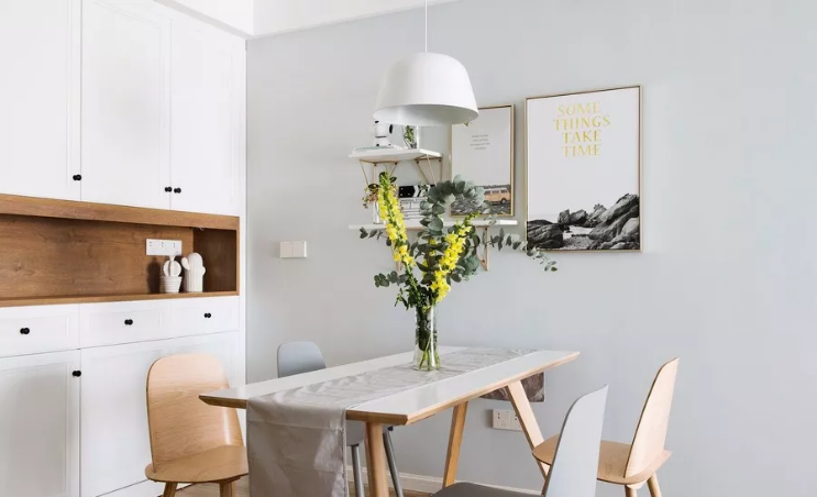 餐桌椅是木色+白色的组合,更有层次感。桌面摆放一瓶绿植,增添无限生机。