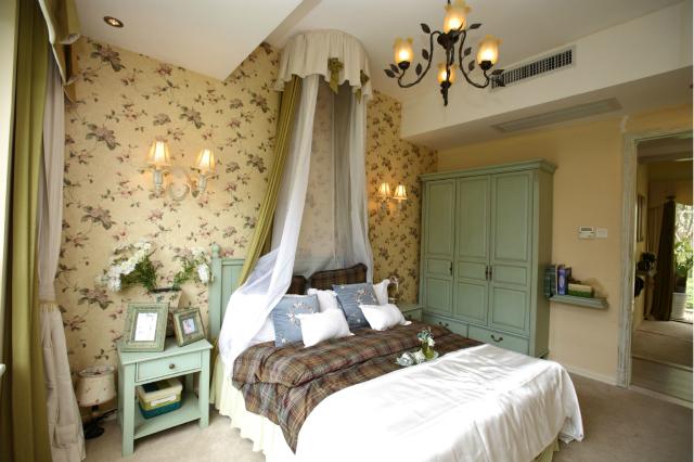 卧室整体展现出一种浓厚的田园风格,碎花的墙纸在灯光的照耀下带着几分大自然的气息。