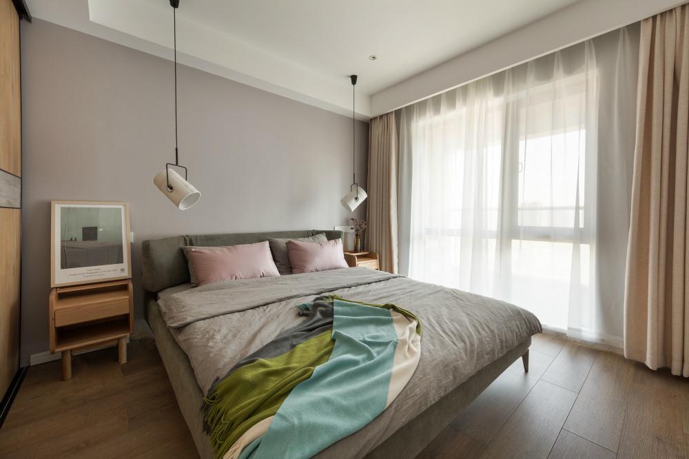 主卧的背景墙选择了淡淡的灰色,,床的一旁是木材的梳妆台,搭配一面方镜,看起来温馨舒适。