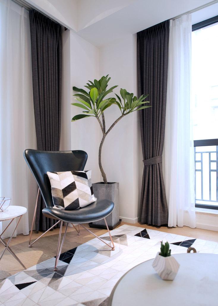 空间里有了绿植就会充满活力,几何地毯和抱枕很搭,黑色皮质单椅质感十足。