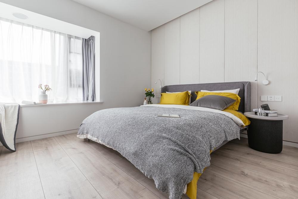 卧室背景墙使用米色设计,富有温润感,局部撞色点缀,营造出舒适的空间氛围。