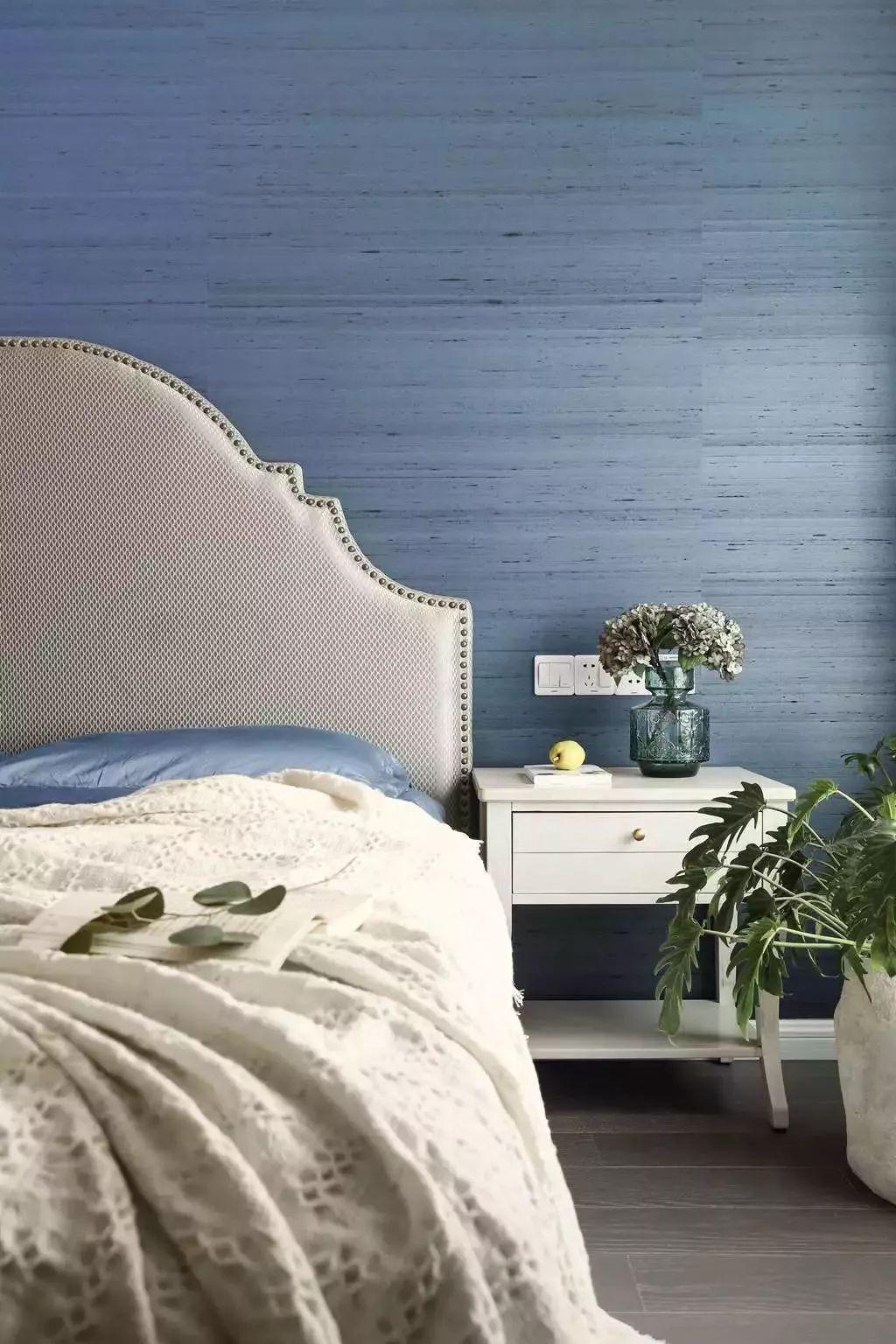 床头背景墙不连续的蓝紫色墙纸,带来起伏的律动美感。配合床边触手可及的满满绿意,呈现出清新空间。