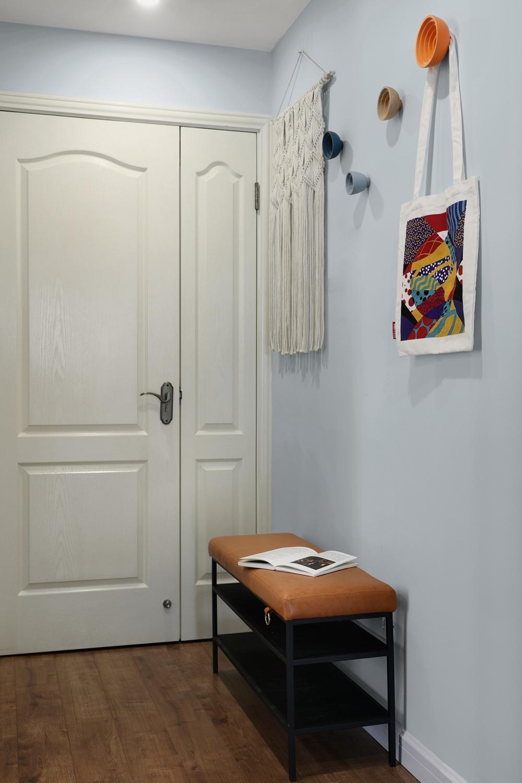 玄关处蓝色墙面和橘色鞋架形成对比,给人带来对比的视觉冲击,增加了现代的气氛。