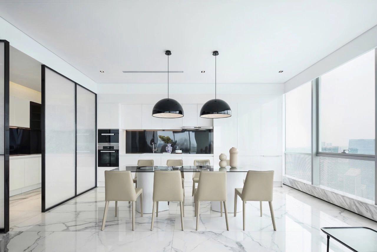 餐廳設計體現出空間的簡約而不簡單,從這個角度可以看到白色的廚房空間。