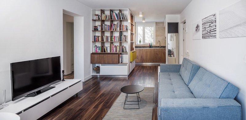 白色墙面与深色木纹地板形成鲜明的色彩对比,蓝灰色的沙发搭配简洁的黑色角几,营造出简约优雅的氛围。