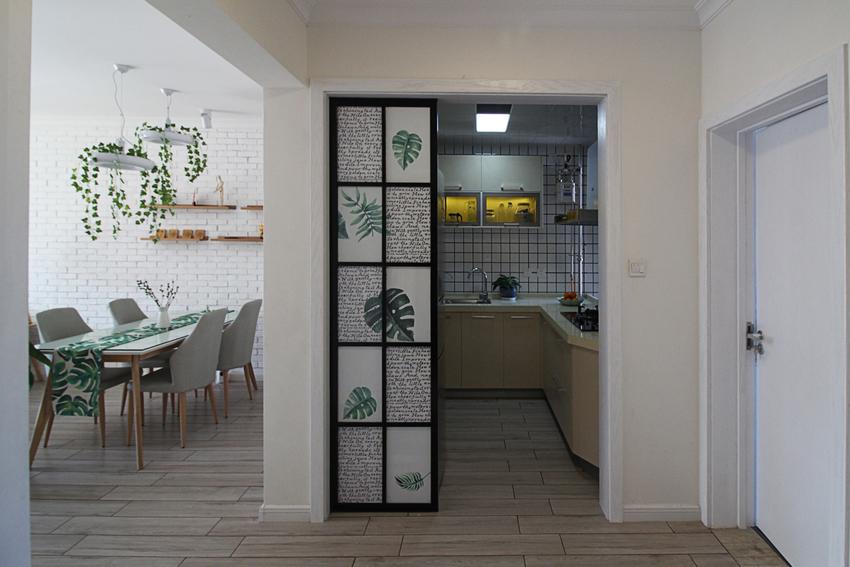 与入户门正对着的是厨房,这里采用了绿植画面的白色不透明门,当拉起来的时候不仅节省空间,还装饰了门面。