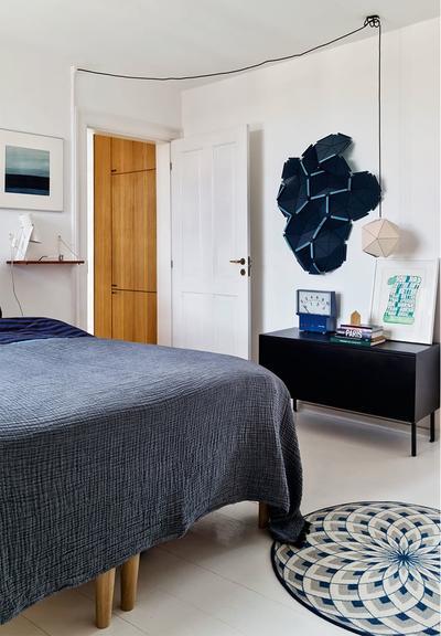 深蓝色的床品在白色空间内静谧内敛,垫子随意的房子床头,吊灯也没有刻意的拉齐,室内处处透着随意的气息。