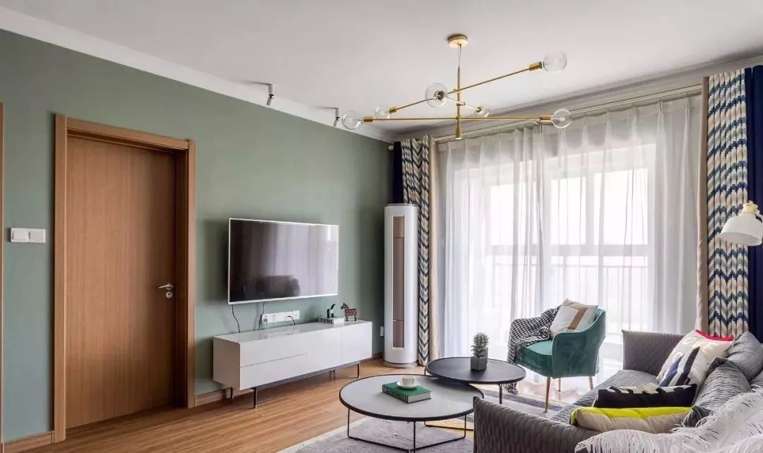 电视背景墙没有过多修饰,纯色壁纸墙面搭配成品电视柜,与木纹套门搭配更显清新自然。