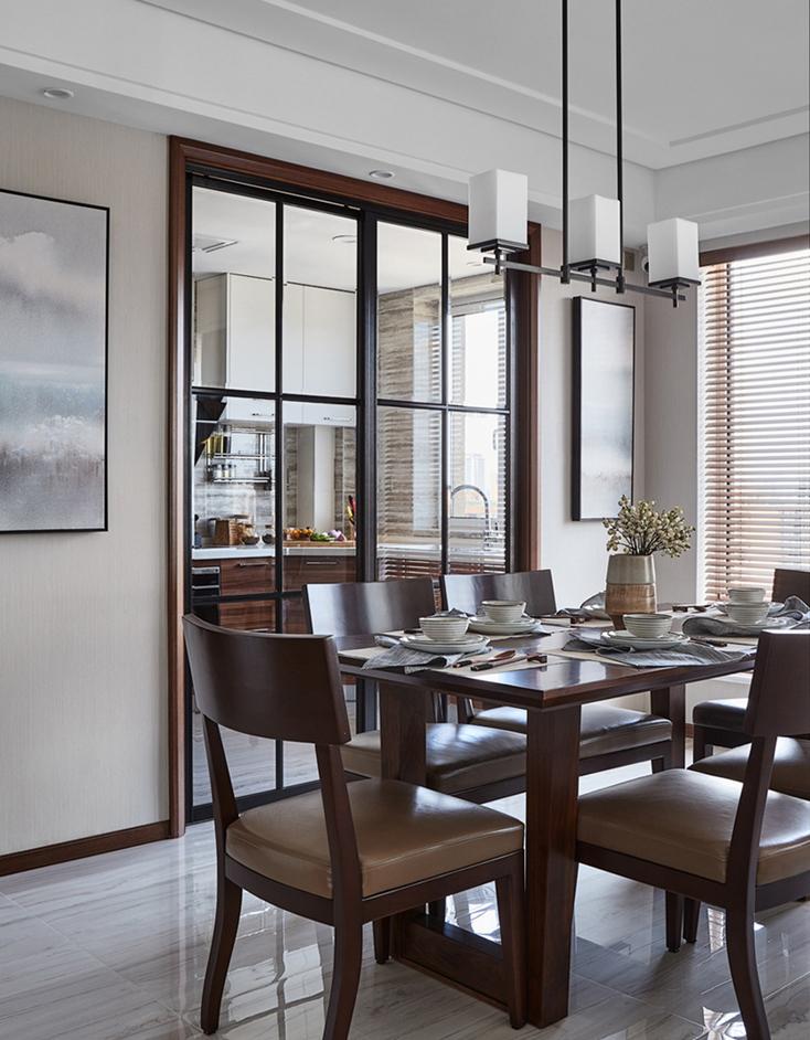 简洁的吊灯形体,硬朗的现代桌椅,朦胧的烟熏画,半透光的百叶窗有点中式格栅的意境。