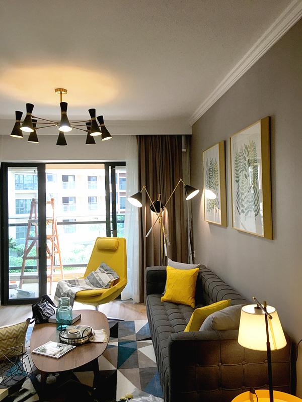 沉稳的木色家具搭配内敛而柔软的灰色沙发、亮黄色靠垫,给人的第一印象是丰富而温馨的。