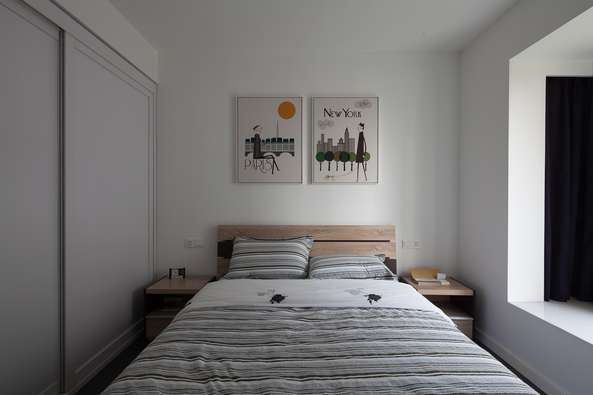 次卧比较简约整洁,床头墙上挂着两幅艺术气息的挂画,以及侧面做了很好的收纳衣柜,整个温馨舒适