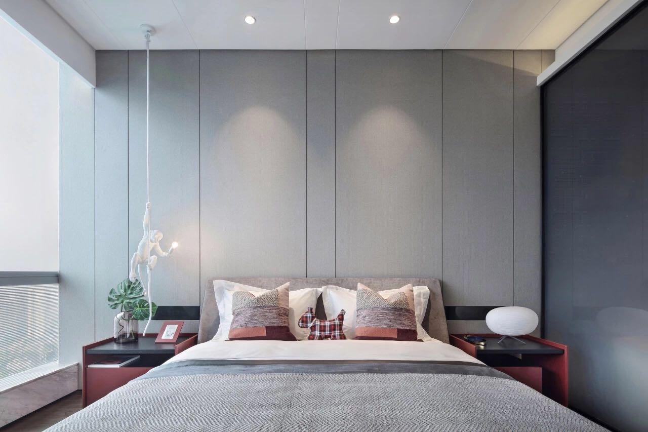 主臥的垂吊燈具打破了灰色帶來的空間單調感受,床品觸感舒適,品質感強烈。