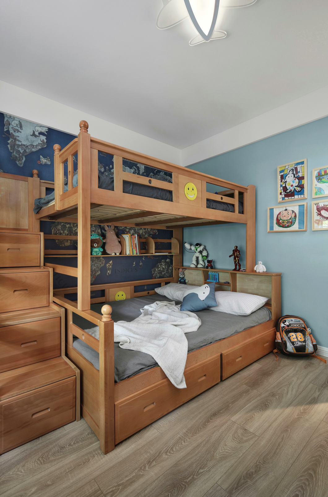 实木上下床提升了空间质感,背景墙采用蓝色设计,让童趣感更显强烈。