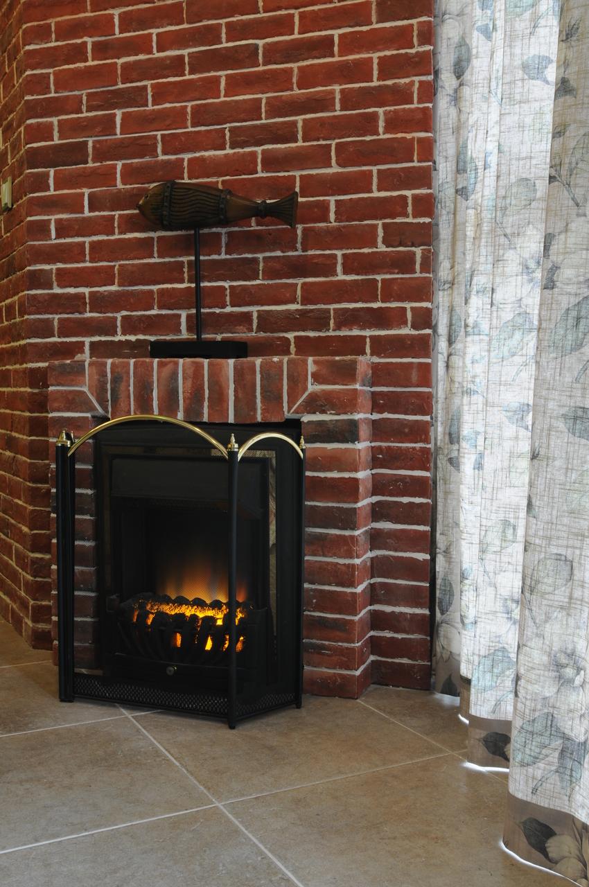 毫无着色的工业风砖墙下是美式的壁炉,和墙角的立柜又成一个风格,让各种风格都不是单一的出现在空间内。