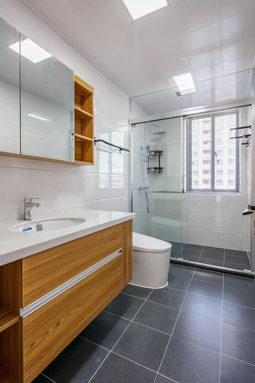 卫生间深色瓷砖地面搭配白色系墙砖,玻璃淋浴房做到干湿分区,木色台盆柜与镜柜呼应整体空间质感。
