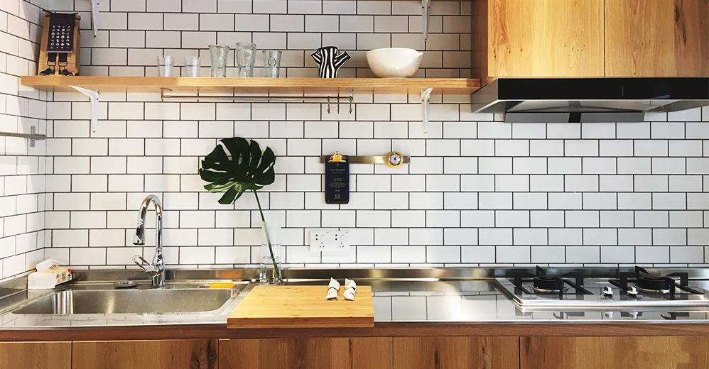 白色墙砖易于反光,镜面不锈钢操作台面为空间增添亮度,厨房空间简洁而功能性强。