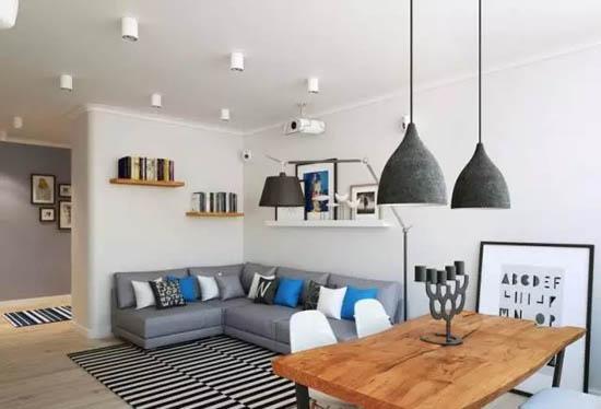 相较于玄关的色彩丰富,客厅以灰、白为主色调,几个蓝色抱枕、一张原木餐桌,简洁明亮。