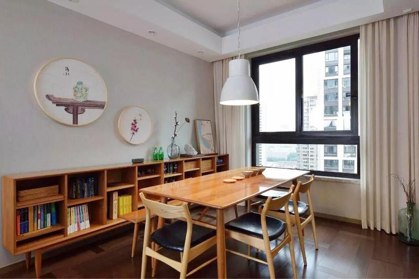 中式风格化的书柜被放置在餐厅的墙边,墙上的话和木质元素带来的是更多古风的感觉。
