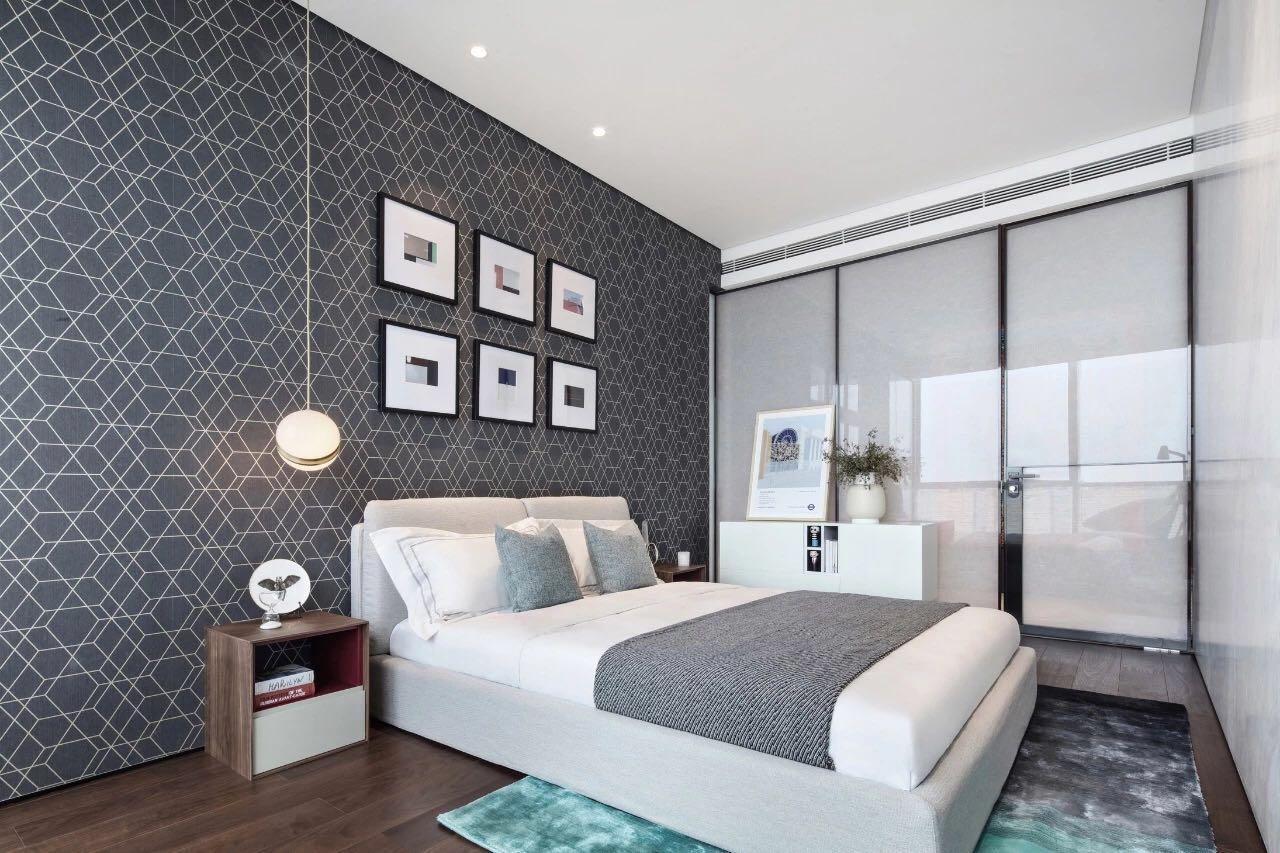 側臥幾何造型背景牆時尚感強,米白色床加上灰白色床品,讓整個空間顯得十分具有律動感。