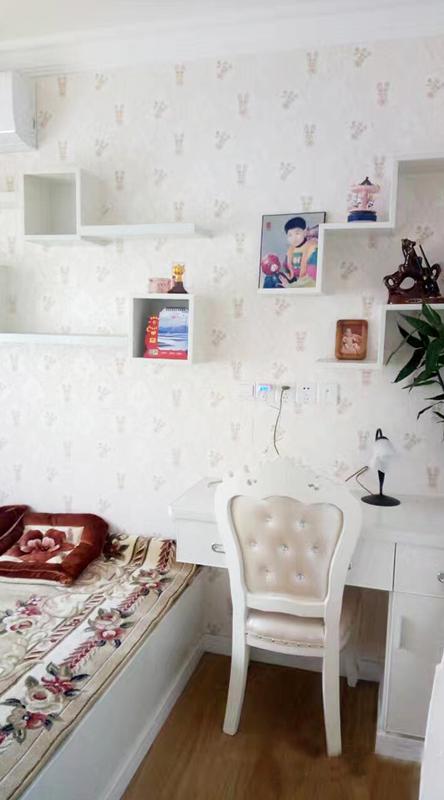 次卧儿童房自成一派小天地,阶梯造型的组合隔板上摆放着小孩子的相片。