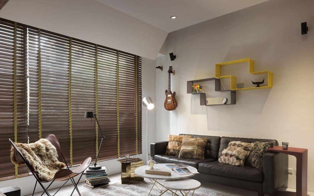 黑色皮质沙发,以及背景的创意格子收纳空间,很是时尚