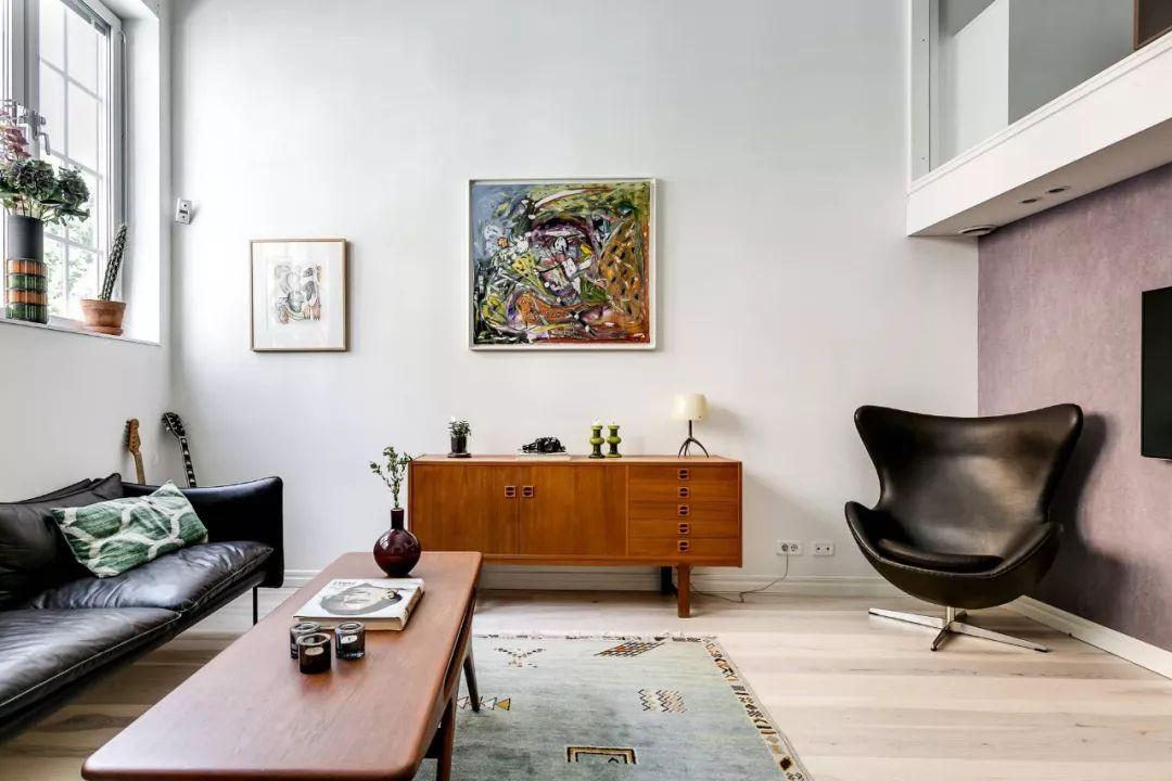 中央位置摆放了棕色的胡桃木茶几,与旁边的躺椅颜色相似,是复古风格常被使用的色彩。