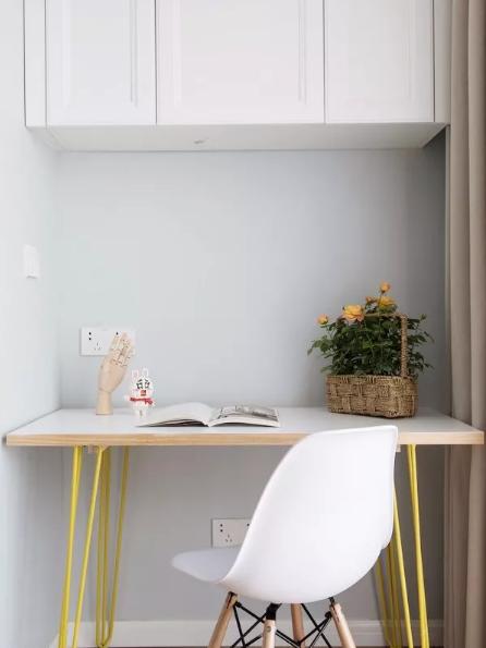 阳台挤出小书房,吊柜的设置补充了收纳。白色桌面和座椅干净整洁,柠檬黄色的桌脚增添了轻盈感。