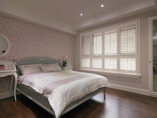 主卧空间很大,粉红碎花背景墙,百叶窗、圆形镜子,清新自然与时尚同在。