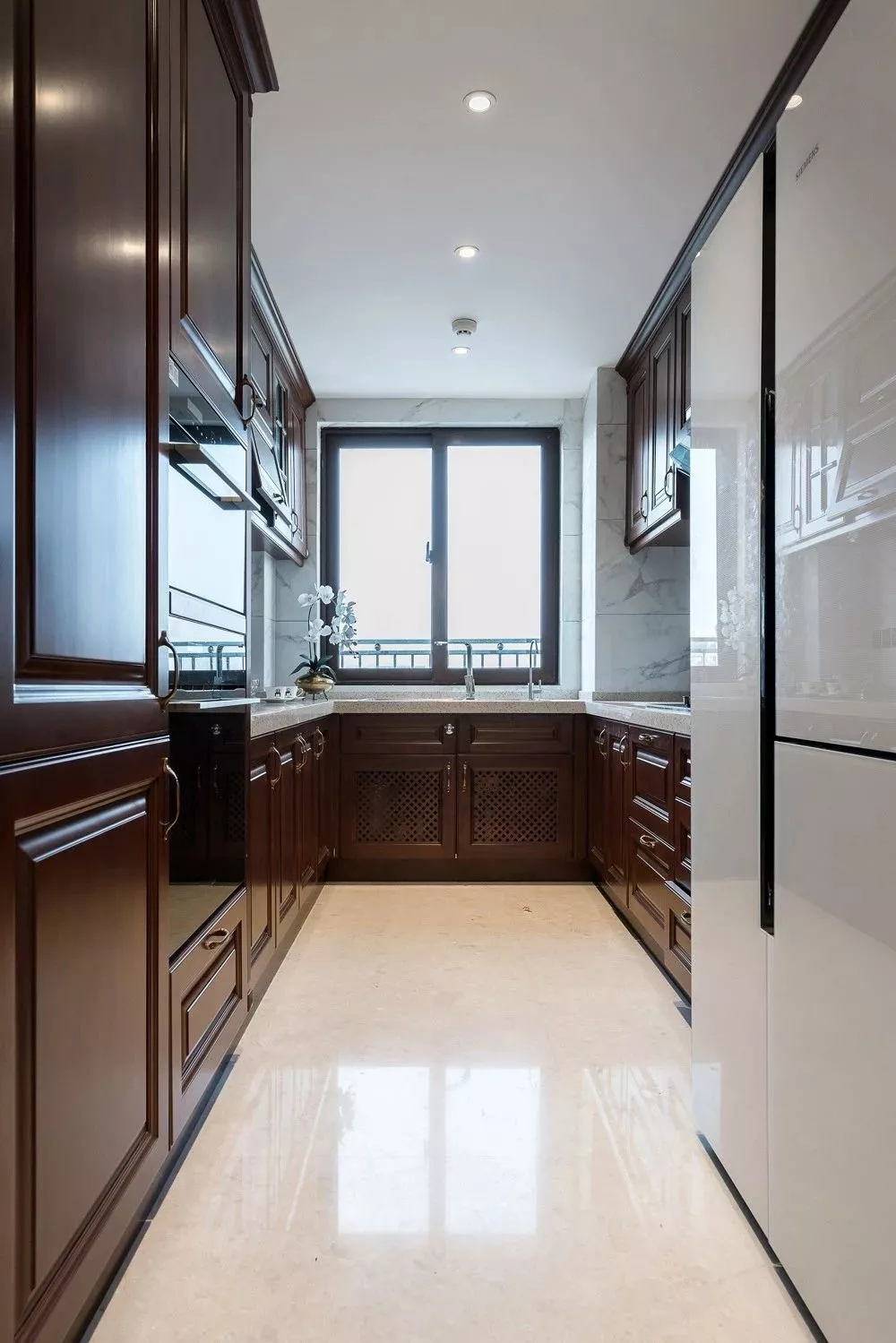 厨房采用了欧式实木柜,从整体到局部都给人满满的华丽高贵之感;阳光透过窗户,整个空间非常敞亮。