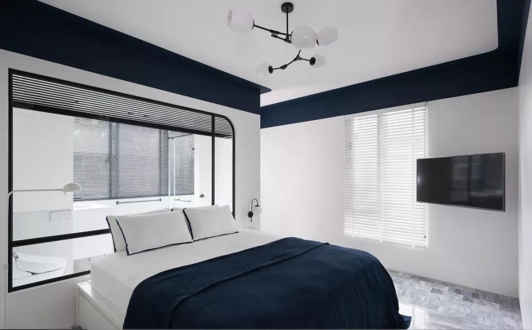 卧室整体以白色为主调,开阔明亮;天花板吊顶与墙面中间以蓝色乳胶漆进行拼接,为空间增添优雅氛围。