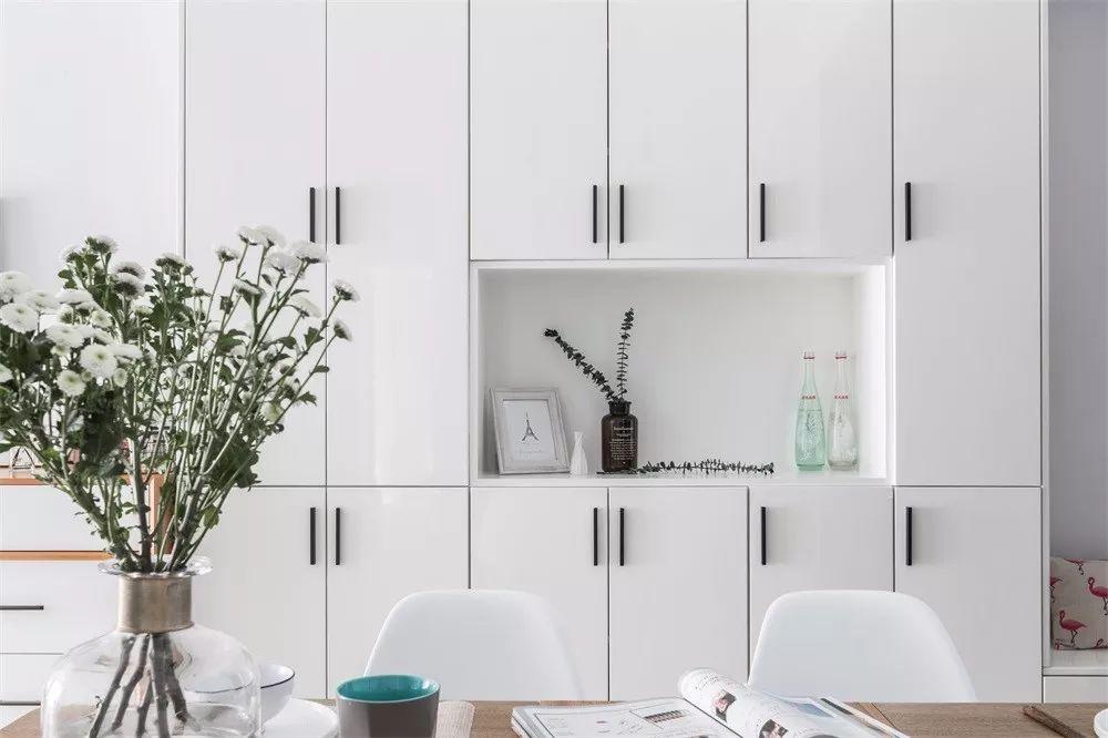 厨房门改动朝向后,两侧的空间都做了顶天立地的柜子充当玄关,纯白的板材搭配一字型的黑色把手,极简风。