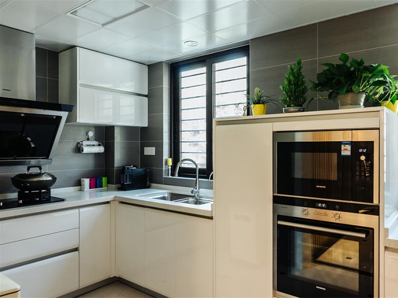 简约型线条的厨房,以干净的白色为主,灶台与洗水盆相邻,方便烹饪。