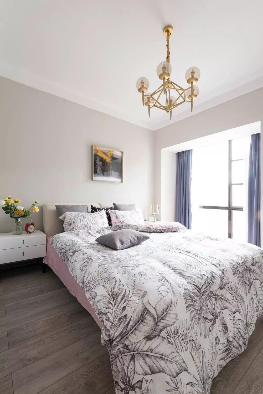 主卧地面通铺木色地板,奶咖色乳胶漆墙面营造柔和氛围。床头一幅金框抽象画与金属质感吊灯呼应,增加质感。