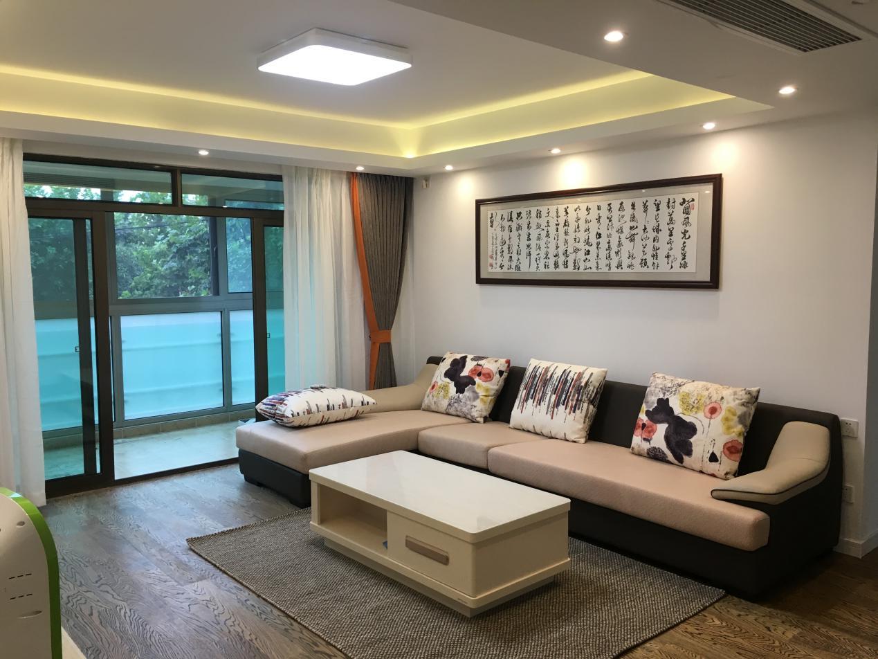 沙发背景墙上挂着书法作品,是业主的业余爱好,让客厅的整体风格更具有文化气息。